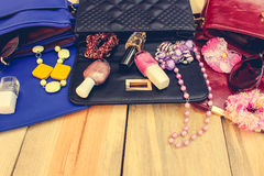 Cosmetics and women's accessories fell out of different handbag. Things from open lady handbag Stock Image