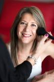 Cosmetólogo que aplica colorete a una mujer joven Fotografía de archivo