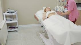 Cosmetología del hardware mujer que consigue procedimiento de elevación del rf en un salón de belleza almacen de metraje de vídeo