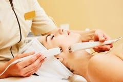 cosmetología Mujer hermosa en la clínica del balneario que recibe el tratamiento facial eléctrico estimulante del terapeuta Close fotografía de archivo libre de regalías