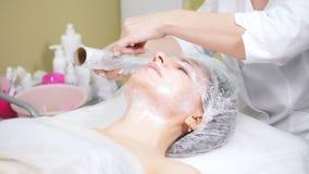 Cosmetologist στο πρόσωπο του πελάτη ταινιών που κάνει τον καλλυντικό καθαρισμό διαδικασιών του προσώπου cosmetology στην κλινική απόθεμα βίντεο
