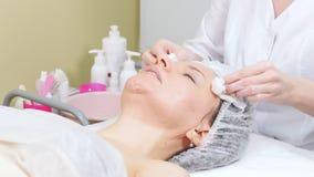 Cosmetologist που τρίβει την κρέμα στα μάγουλα του πελάτη που κάνουν τον καλλυντικό καθαρισμό διαδικασιών του προσώπου cosmetolog φιλμ μικρού μήκους