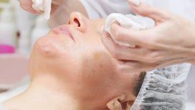 Cosmetologist που τρίβει την κρέμα στο πρόσωπο του πελάτη που κάνει τον καλλυντικό καθαρισμό διαδικασιών του προσώπου cosmetology απόθεμα βίντεο
