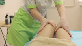Cosmetologist мажет ноги женщин со сливк и делает расслабляющий массаж после epilation сток-видео
