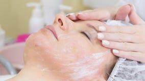 Cosmetologist που εφαρμόζει την κρέμα στο πρόσωπο του πελάτη που κάνει τον καλλυντικό καθαρισμό διαδικασιών του προσώπου cosmetol απόθεμα βίντεο