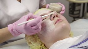 Cosmetologist που εφαρμόζει την του προσώπου μάσκα στο δέρμα προβλήματος νέα γυναίκα που έχει τον καθαρισμό διαδικασιών δερμάτων απόθεμα βίντεο