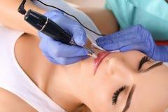 Cosmetologist που κάνει το μόνιμο makeup στα χείλια γυναικών ` s στοκ εικόνες