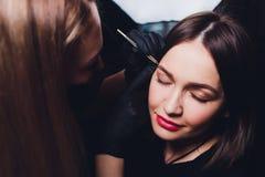 Cosmetologist που κάνει το σχέδιο φρυδιών Ελκυστική γυναίκα που παίρνει την του προσώπου προσοχή στο σαλόνι ομορφιάς Τέλεια αρχιτ στοκ φωτογραφίες
