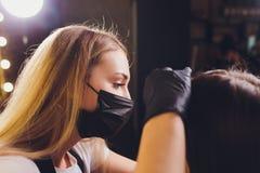 Cosmetologist που κάνει το σχέδιο φρυδιών Ελκυστική γυναίκα που παίρνει την του προσώπου προσοχή στο σαλόνι ομορφιάς Τέλεια αρχιτ στοκ φωτογραφία με δικαίωμα ελεύθερης χρήσης