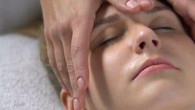 Cosmetologist που τρίβει ήπια το πρόσωπο, χαλάρωση γυναικών luxury spa, προσοχή σωμάτων φιλμ μικρού μήκους