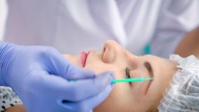 Cosmetologist στο άσπρο παλτό εργαστηρίων που εφαρμόζει τον εγχυτήρα ή degreaser brow που χρησιμοποιεί το βούρτσισμα μικροϋπολογι απόθεμα βίντεο