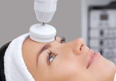 Cosmetologist делает прибором процедуру чистки стороны оборудования с мягкой вращая щеткой Стоковое фото RF
