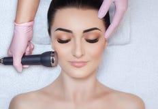 Cosmetologist делает процедурой ультразвуковую чистку лицевой кожи красивого, молодой женщины в салоне красоты стоковое фото rf