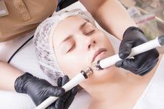 Cosmetologist делает процедуру по прибора терапии красивого, молодой женщины Microcurrent в салоне красоты стоковые изображения rf