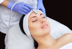 Cosmetologist делает процедуру Microdermabrasion лицевой кожи красивого, молодой женщины в салоне красоты стоковые фотографии rf
