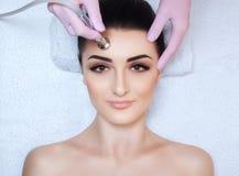 Cosmetologist делает процедуру Microdermabrasion лицевой кожи красивого, молодой женщины в салоне красоты стоковая фотография rf