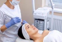 Cosmetologist делает терапию Microcurrent процедуры лицевой кожи красивого, молодой женщины в салоне красоты стоковые изображения