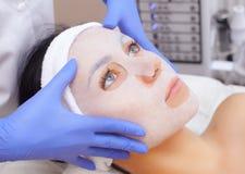 Cosmetologist для процедуры очищать и moisturizing кожу, прикладывая маску листа к стороне молодой женщины стоковая фотография