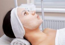 Cosmetologist для процедуры очищать и moisturizing кожу, прикладывая маску листа к стороне молодой женщины стоковые фото