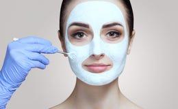 Cosmetologist для процедуры очищать и moisturizing кожу, прикладывая маску с ручкой к стороне молодого woma стоковое изображение rf