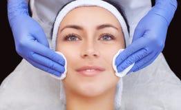 Cosmetologist доктора очищает с тоникой кожу красивого, молодую женщину стороны в салоне красоты стоковое фото