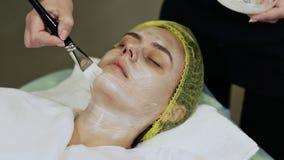Cosmetologist женщины для того чтобы приложить сливк-маску на стороне Чистка косметических процедур механически стороны сток-видео