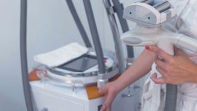 Cosmetologist займет и включает прибор для массажа lpg Подготовка для массажа lpg Конец-вверх рук сток-видео