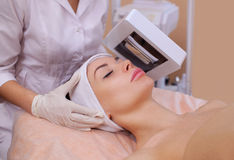 Cosmetologist диагностирует с деревянным кожным заболеванием лампы ` s, и также показывает воспламененные зоны на стороне Стоковые Изображения RF