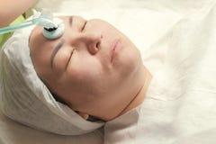 Cosmetologist использует прибор с пульсированными переменными токами частоты коротковолнового диапазона Darsonvalization Конец-вв стоковые изображения