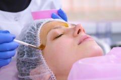 Cosmetologist кладет химическое шелушение стороны женщины с щеткой Очищать кожу стороны и облегчать кожу веснушек стоковые фотографии rf