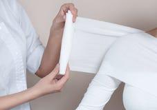 Cosmetologist оборачивает оружия и тело клиента стоковое фото rf