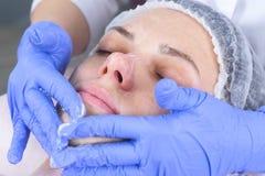 Cosmetologist обтирает сторону молодой женщины с пусковыми площадками хлопка Руки beautician в перчатках и крупном плане стороны стоковые фото