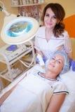 Cosmetologist доктора делает процедурой женщину на стороне курорта стоковые изображения rf