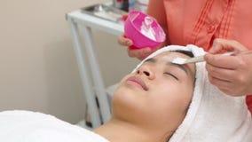 Cosmetologist прикладывает лицевую сторону женщины маски сток-видео