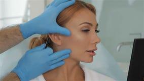 Cosmetologist протягивает кожу на щеке клиента акции видеоматериалы