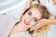 Cosmetologist applaying anti-aging eye gel pads Royalty Free Stock Images