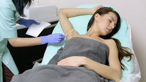 Cosmetologist applies gel to armpits of patient before epilation procedure stock video