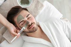 Cosmetologist appliquant le masque sur le visage du client dans le salon de station thermale, image libre de droits