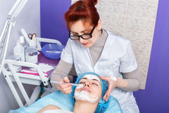 Cosmetologist applying mask on the face Stock Image
