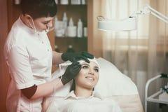 Cosmetologist applying permanent make up on eyebrows- eyebrow tattoo Stock Photo