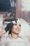Cosmetologist applying permanent make up on eyebrows- eyebrow tattoo Stock Photos