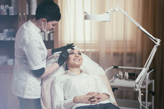 Cosmetologist applying permanent make up on eyebrows- eyebrow tattoo Royalty Free Stock Images