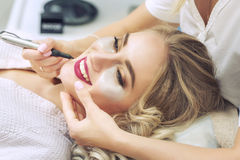 Cosmetologist applying permanent make-up on lips. Woman smiling at cosmetic salon Stock Photography