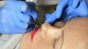 Cosmetologist applying permanent make-up. Young beautiful woman having cosmetic tattoo on her lips. Healthy Spa