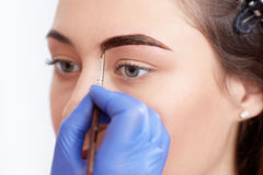 Cosmetologist applying special permanent make up of eyebrows. stock photos