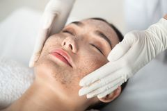 Cosmetologist arms applying peeling mask on female face. Close up of asian girl enjoying skin care treatment. Beautician hands pampering her face with scrub Stock Photo