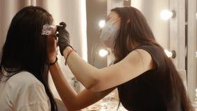 Cosmetologist bedeckt die Augenbrauen stock video footage