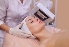 Cosmetologist bestimmen mit hölzerner ` s Lampen-Hautkrankheit und decken auch entflammte Bereiche auf dem Gesicht auf Lizenzfreie Stockbilder