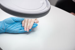 Cosmetologist is checking cuticles of young woman. Nails health. Specialist is sitting at workplace in blue gloves. Close up top view of hands of client and Stock Photography