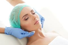 Cosmetologist cleaning face of a young woman with a cotton pads. Removing cosmetics with hygienic discs. Cosmetology concept royalty free stock photo